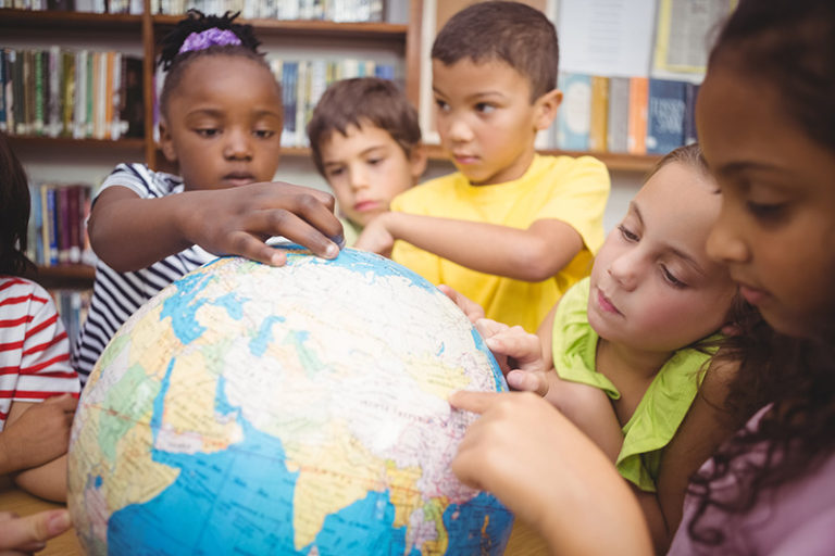 Primary school aged children pointing at countries on a world globe