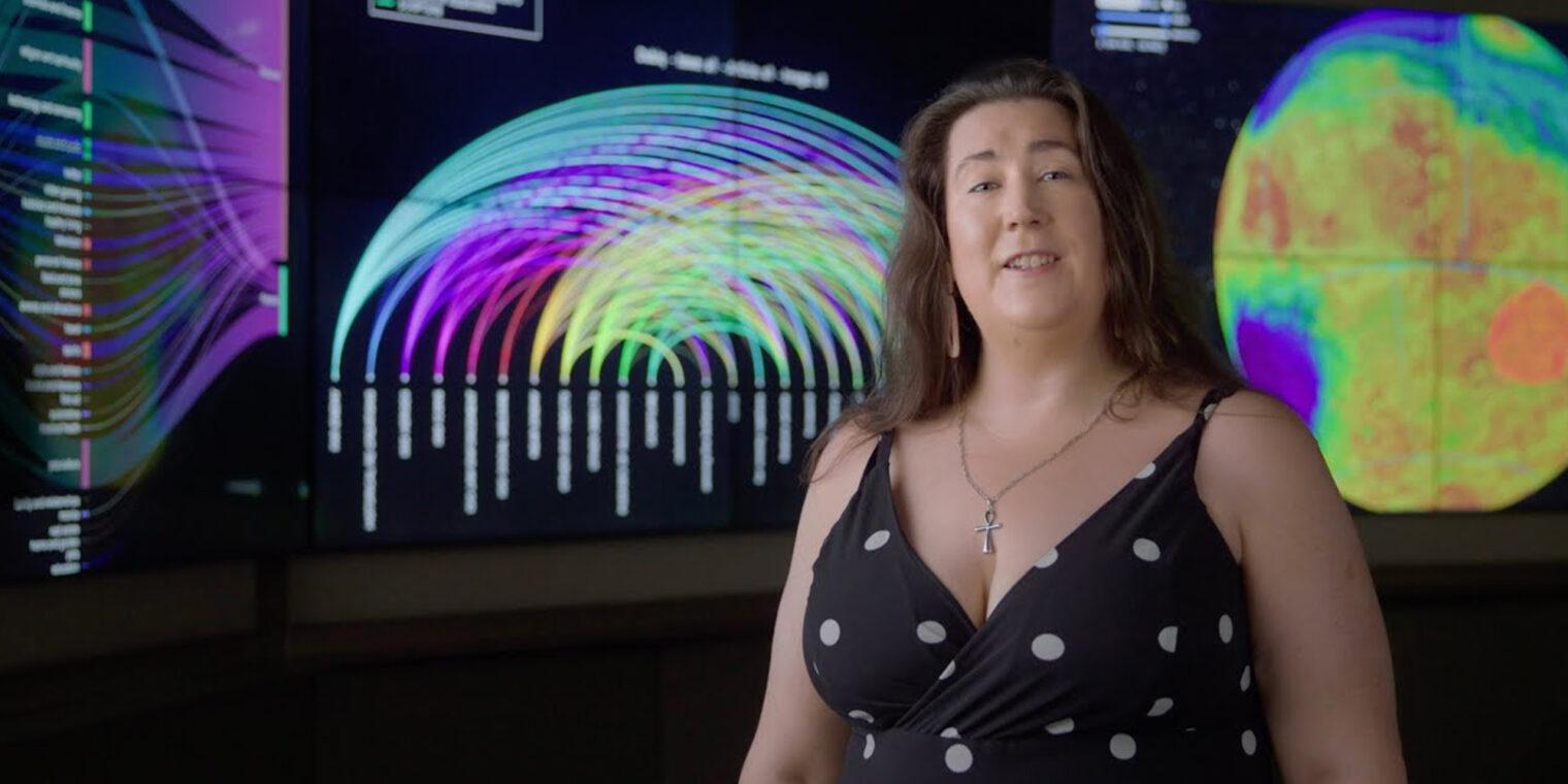 Professor Melanie Johnston-Hollitt standing in front of large data-visualisation screens - play video